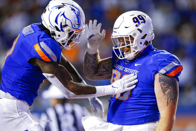 Boise State defensive tackle Scott Matlock (99) celebrates with safety JL Skinner (0) after recovering a fumble by UTEP quarterback Gavin Hardison during the first half of an NCAA college football game Friday, Sept. 10, 2021, in Boise, Idaho. (AP Photo/Steve Conner)