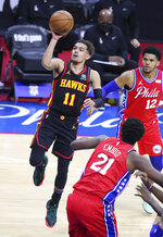 Atlanta Hawks guard Trae Young (11) goes to the basket for two points past Philadelphia 76ers center Joel Embiid and forward Tobias Harris during the second half of an NBA basketball second-round Eastern Conference playoff game on Sunday, Jun 6, 2021, in Philadelphia. (Curtis Compton/Atlanta Journal-Constitution via AP)