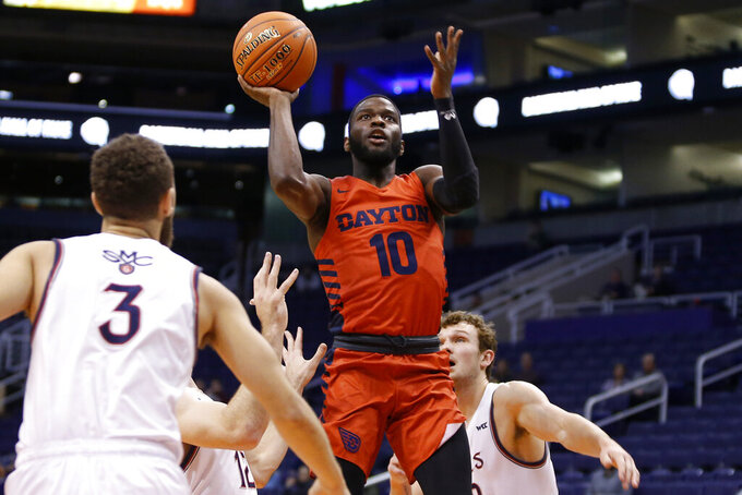Dayton guard Jalen Crutcher (10) shoots the ball over the defense of Saint Mary's Jordan Ford (3), Tommy Kuhse (12) and Tanner Krebs, right, during the first half of an NCAA college basketball game, Sunday, Dec. 8, 2019, in Phoenix. (AP Photo/Ralph Freso)