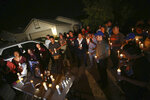 FILE - In this Nov. 18, 2019 file photo friends and family of shooting victim Kou Xiong gather in front of his home for a candle light vigil in Fresno, Calif. Police in California announced Tuesday, Dec. 31, 2019, they have arrested six suspected gang members in the shooting deaths of four men last month at a backyard gathering of family and friends. (Larry Valenzuela/The Fresno Bee via AP,File)