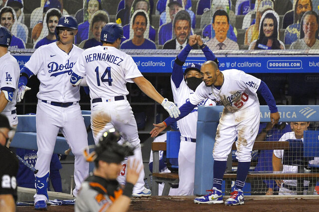 Los Angeles Dodgers' Kiké Hernández (14) is congratulated by Mookie Betts, right, Joc Pederson, left, and manager Dave Roberts after hitting a two-run home run during the eighth inning of an opening day baseball game, Thursday, July 23, 2020, in Los Angeles. (AP Photo/Mark J. Terrill)