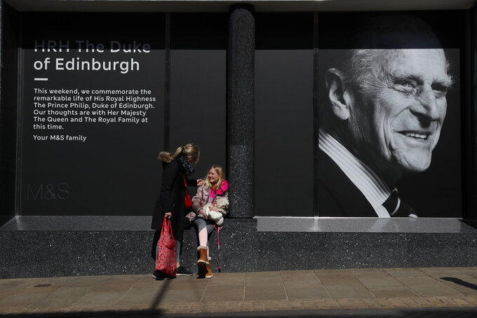 Isabella Disley greets her mother Tara Lynn and her dog Coco next to a portrait of Prince Philip, which adorns a window of a department store in Windsor, England, Friday, April 16, 2021. Prince Philip husband of Britain's Queen Elizabeth II died April 9, aged 99, his funeral will take place Saturday at Windsor Castle in St George's Chapel. (AP Photo/Alastair Grant)