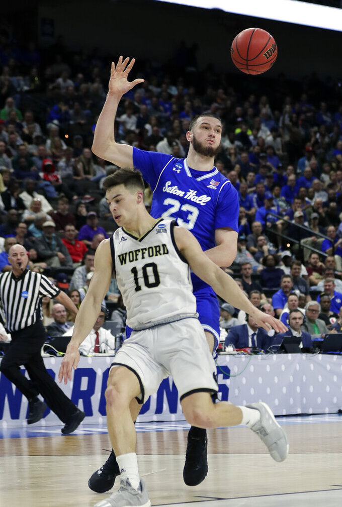 Seton Hall's Sandro Mamukelashvili (23) passes the ball over Wofford's Nathan Hoover (10) during the first half of a first-round game in the NCAA men's college basketball tournament in Jacksonville, Fla., Thursday, March 21, 2019. (AP Photo/John Raoux)