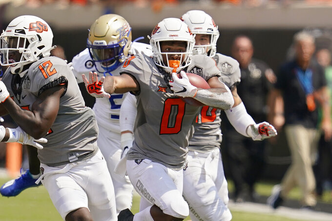 Oklahoma State running back LD Brown (0) carries a kick-off return 98-yards for a touchdown in the second half of an NCAA college football game against Tulsa,, Saturday, Sept. 11, 2021, in Stillwater, Okla. (AP Photo/Sue Ogrocki)