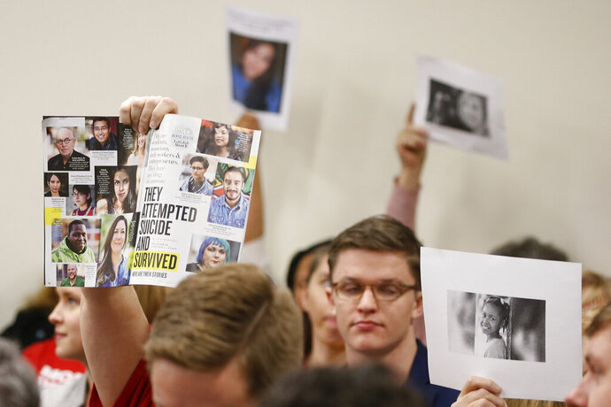 Supporters of gun laws hold us photos of gun violence victims during the meeting of the Senate Judiciary committee at the Capitol in Richmond, Va., Monday, Jan. 13, 2020. The Committee passed several gun related bills. (AP Photo/Steve Helber)