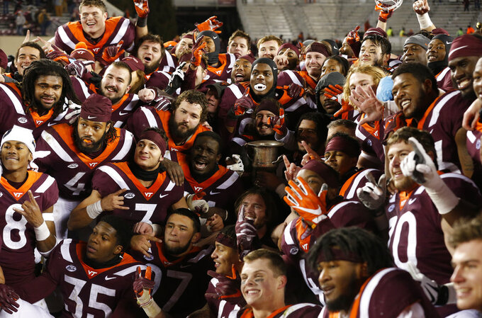 Members of the Virginia Tech football team celebrate their overtime win over Virginia after an NCAA college football game in Blacksburg, Va., Friday, Nov. 23, 2018. Virginia Tech defeated Virginia 34-31. (AP Photo/Steve Helber)