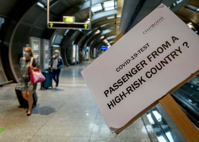 A sign helps passengers to find the Cover-19 test center at the airport in Frankfurt, Germany, Saturday, Aug. 8, 2020. From Saturday on Covid-19 tests are mandatory for passengers coming from a high-risk-country. (AP Photo/Michael Probst)