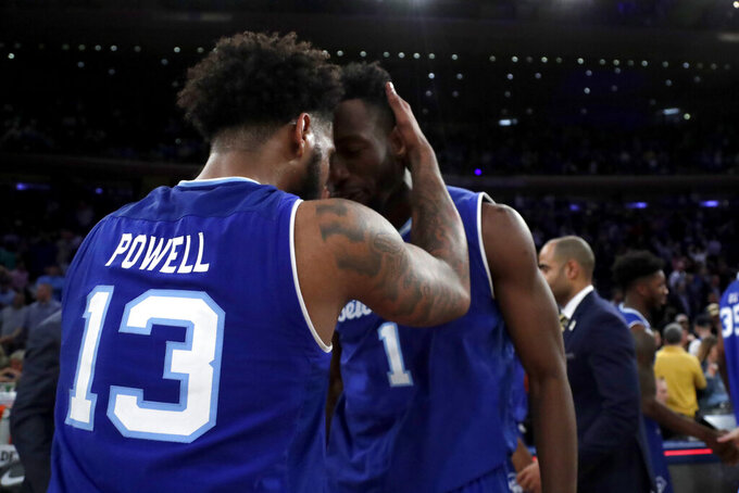 Seton Hall guard Myles Powell (13) and forward Michael Nzei share a moment after defeating Marquette in an NCAA college basketball semifinal game in the Big East men's tournament, early Saturday, March 16, 2019, in New York. Seton Hall won 81-79. (AP Photo/Julio Cortez)