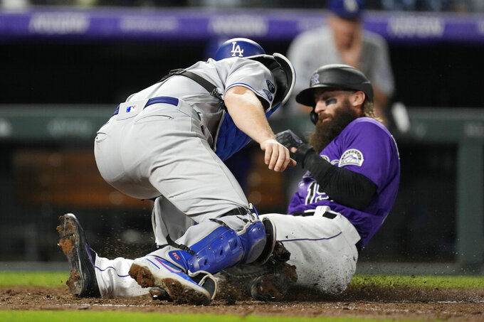 Los Angeles Dodgers catcher Will Smith, front, applies a late tag as Colorado Rockies' Charlie Blackmon scores on a double hit by C.J. Cron in the seventh inning of a baseball game Wednesday, Sept. 22, 2021, in Denver. (AP Photo/David Zalubowski)