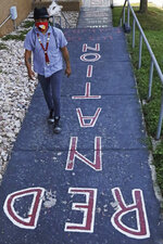 Native American advocate Carl Moore walks along a walkway which leads from the Bountiful High School parking lot up to the football field Tuesday, July 28, 2020, in Bountiful, Utah. While advocates have made strides in getting Native American symbols and names changed in sports, they say there's still work to do mainly at the high school level, where mascots like Braves, Indians, Warriors, Chiefs and Redskins persist. (AP Photo/Rick Bowmer)