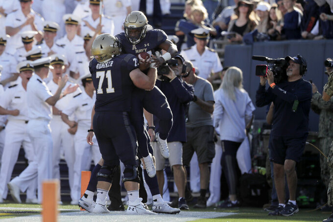 Navy fullback Nelson Smith, right, is lifted by offensive tackle Billy Honaker after scoring on a touchdown run against Air Force during the first half of an NCAA college football game Saturday, Oct. 5, 2019, in Annapolis, Md. (AP Photo/Julio Cortez)