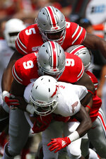 Ohio State defenders Baron Browning, top, and Jashon Cornell, tackle Florida Atlantic receiver Willie Wright during the first half of an NCAA college football game Saturday, Aug. 31, 2019, in Columbus, Ohio. (AP Photo/Jay LaPrete)