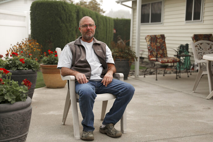 Don Myron poses for a photo at his mother's home in Woodburn, Ore., on Tuesday, Sept. 15, 2020. Myron says he used a green plastic chair as a shield from a huge, deadly wildfire as he sheltered from the flames on a rock in the middle of a river.