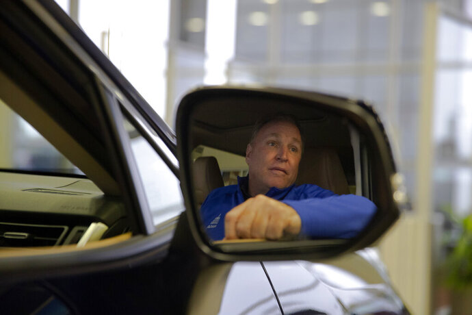 """Howard Hakes, chairman of the American International Automobile Dealers Association, poses in a 2019 Toyota RAV4 manufactured in Japan at his dealership Thursday, Feb. 14, 2019, in Industry, Calif. If 25 percent tariffs are fully assessed against imported parts and vehicles, and they include Canada and Mexico, the price of imported vehicles would rise more than 17 percent, or around $5,000 each, according to forecasts from IHS Markit. """"I think it would be harmful to the whole economy,"""" said Hakes. (AP Photo/Jae C. Hong)"""