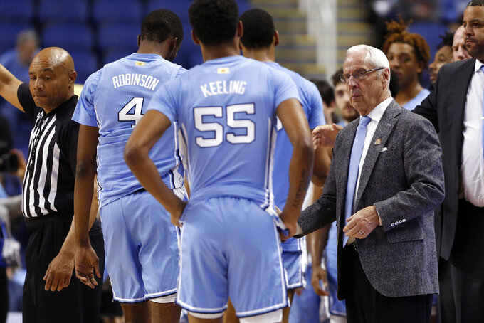 North Carolina head coach Roy Williams shakes hands with his players following an NCAA college basketball game against Syracuse at the Atlantic Coast Conference tournament in Greensboro, N.C., Wednesday, March 11, 2020. (AP Photo/Ben McKeown)