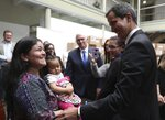 Venezuela's self-proclaimed interim president Juan Guaido visits with a Venezuelan migrant and her daughter, in Bogota, Colombia, Monday, Feb. 25, 2019. Guaido in his visit to the Colombian capital was afforded all the trappings of a head of state. He posed for selfies with well-wishers upon arriving for or an emergency summit of regional leaders and stood before a pile of aid boxes stamped with the U.S. flag as he and Vice President Pence greeted a group of Venezuelan migrants. (AP Photo/Martin Mejia)