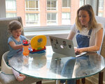 "In this May 15, 2020 image, Blake Ross, founder of Kindness of Strangers, right, works on her laptop as her daughter, Tess, 2, works on her toy laptop in New York. Ross has partnered with Enlivant, which runs senior homes in 20 states, and has set up an Adopt a Grandparent program. ""The essence of volunteering is that you feel wonderful after giving of yourself,"