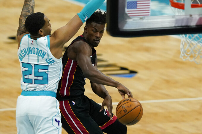 Miami Heat forward Jimmy Butler, right, passes around Charlotte Hornets forward P.J. Washington during the first half of an NBA basketball game on Sunday, May 2, 2021, in Charlotte, N.C. (AP Photo/Chris Carlson)