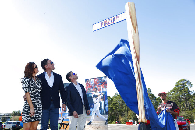 Former New York Mets catcher Mike Piazza, center left, his wife Alicia, left, and Mets COO Jeff Wilpon watch as newly named Piazza Dr., is unveiled during a ceremony in front of the Mets spring training facility, Thursday, Jan. 16, 2020, in Port St. Lucie, Fla. (AP Photo/Wilfredo Lee)