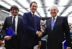 FCA Chairman John Elkann, center, shakes hands with former Italian Premier Mario Monti, right, as Bocconi University Rector Gianmario Verona stands by them, in Milan, Italy, Monday, May 27, 2019. Fiat Chrysler is proposing a merger with French carmaker Renault aimed at saving billions of dollars for both companies. Shares of both companies jumped on the possibility. (AP Photo/Antonio Calanni)