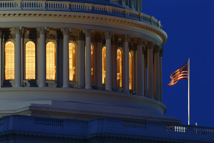 FILE - In this July 16, 2019, file photo an American flag flies on the Capitol Dome in Washington. The U.S. budget deficit climbed to $2.81 trillion in the first 10 months of the budget year, exceeding any on record, the Treasury Department said Wednesday, Aug. 12, 2020. (AP Photo/Carolyn Kaster, File)
