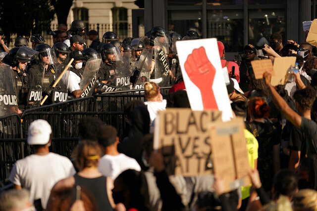 Demonstrators stand in front of police in riot gear as they gather to protest the death of George Floyd, Saturday, May 30, 2020, near the White House in Washington. Floyd died after being restrained by Minneapolis police officers. (AP Photo/Evan Vucci)