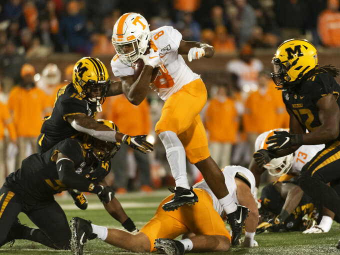 Tennessee running back Ty Chandler, center, leaps between Missouri defenders Nick Bolton, right, Joshuah Bledsoe, top left, and Devin Nicholson, bottom left, during the second quarter of an NCAA college football game Saturday, Nov. 23, 2019, in Columbia, Mo. (AP Photo/L.G. Patterson)