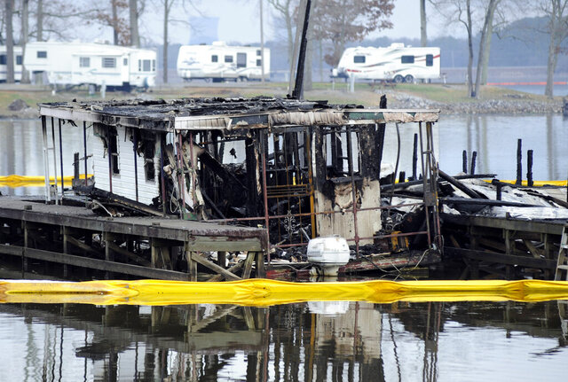 "FILE - In this Jan. 27, 2020 file photo, the charred remains of a boat are shown following a fatal fire at a Tennessee River marina in Scottsboro, Ala. Federal investigators agree with state investigators that a fire that killed eight people and did more than $500,000 damage in January at an Alabama marina started accidentally. But the National Transportation Safety Board says the fire was made worse by the marina's ""limited fire safety practices.""  (AP Photo/Jay Reeves, File)"