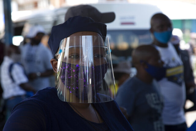 FILE — In this Thursday, Dec. 24, 2020 file photo people wear face masks to protect against COVID-19 before boarding a minibus taxi in Johannesburg. In a television address to the nation Monday, Dec. 28, 2020, President Cyril Ramaphosa announced that the country would revert to level 3 of a strict lockdown in a bid to control a surge in the virus and it would be compulsory to wear face masks in public. (AP Photo/Denis Farrell/File)