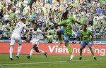 Portland Timbers forward Brian Fernandez, left, kicks a goal as forward Jeremy Ebobisse, second from left, as Seattle Sounders' defenders Roman Torres (29) and Kelvin Leerdam, right, look on during the first half of an MLS soccer match, Sunday, July 21, 2019, in Seattle. (AP Photo/Ted S. Warren)