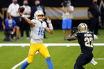 Los Angeles Chargers quarterback Justin Herbert (10) passes under pressure from New Orleans Saints strong safety Malcolm Jenkins (27) in the first half of an NFL football game in New Orleans, Monday, Oct. 12, 2020. (AP Photo/Brett Duke)