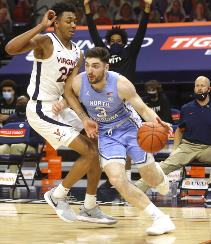 North Carolina guard Andrew Platek (3) moves past Virginia guard Trey Murphy III (25) during an NCAA college basketball game Saturday, Feb. 13, 2021, in Charlottesville, Va. (Andrew Shurtleff/The Daily Progress via AP, Pool)