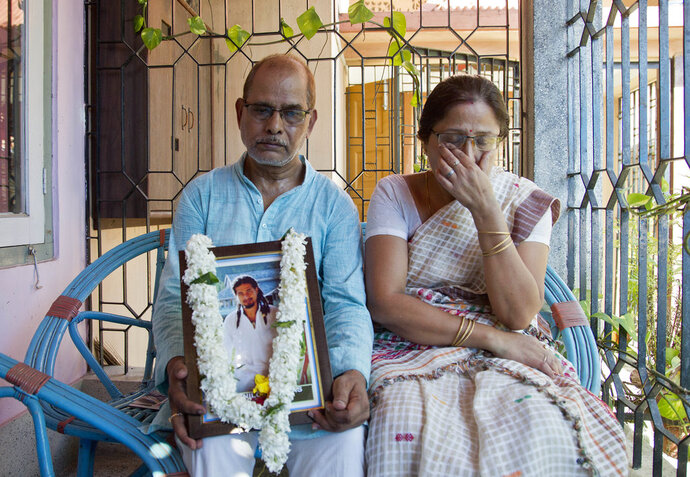 In this Monday, June 11, 2018 photo, Gopal Chandra Das, left and Radhika Das, parents of Nilotpal Das, who was killed in a mob attack hold his photograph during a ritual at his residence in Gauhati, India. Fueled by rumors of child kidnappers, and spread on social media, Indian mobs have killed well over a dozen people in brutal attacks since early May. (AP Photo/Anupam Nath)