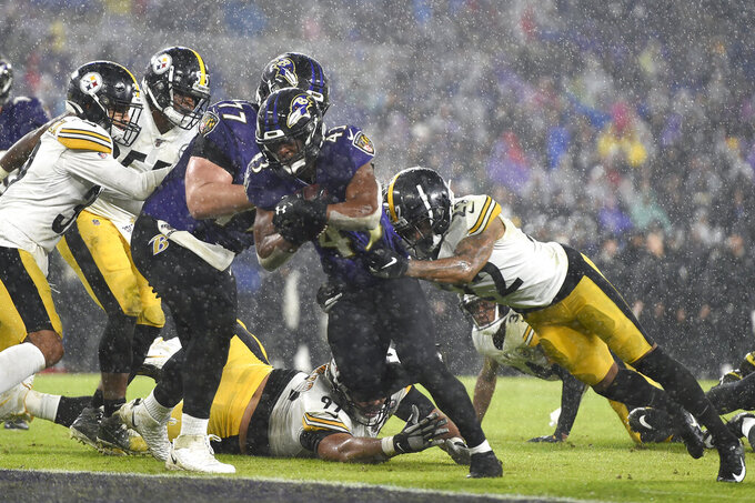 Baltimore Ravens running back Justice Hill (43) rushes in for a touchdown as Pittsburgh Steelers cornerback Steven Nelson (22) tries to stop him during the first half of an NFL football game, Sunday, Dec. 29, 2019, in Baltimore. (AP Photo/Gail Burton)