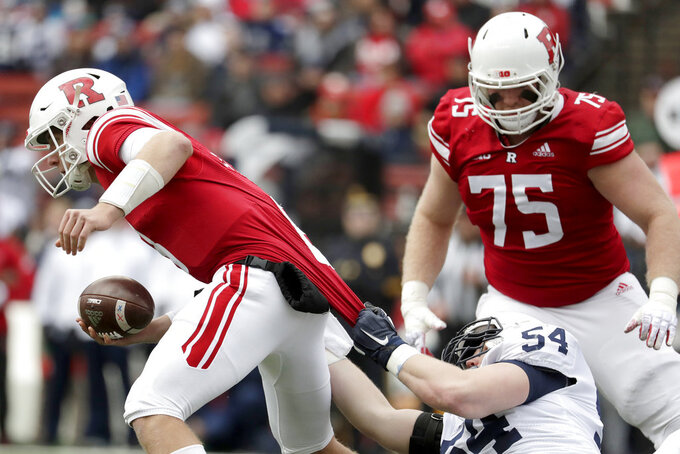 Penn State defensive tackle Robert Windsor, bottom right, grabs at the jersey of Rutgers quarterback Artur Sitkowski, left, while recording a sack during the first half of an NCAA college football game, Saturday, Nov. 17, 2018, in Piscataway, N.J. Rutgers' Zach Venesky (75) looks on during the play. (AP Photo/Julio Cortez)