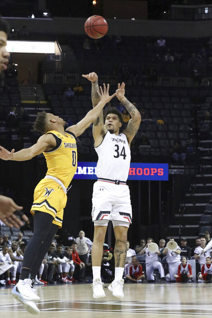 Wichita State player Dexter Dennis try to defend as Cincinnati's Jarron Cumerland shoots for three in the first half of an NCAA college basketball game at the American Athletic Conference tournament Saturday, March 16, 2019, in Memphis, Tenn. (AP Photo/Troy Glasgow)