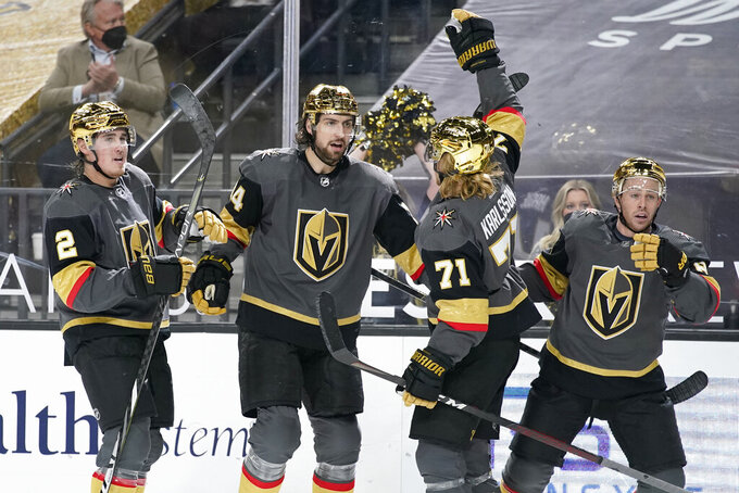 Vegas Golden Knights celebrate after defenseman Nicolas Hague, second from left, scored against the Los Angeles Kings during the second period of an NHL hockey game Monday, March 29, 2021, in Las Vegas. (AP Photo/John Locher)