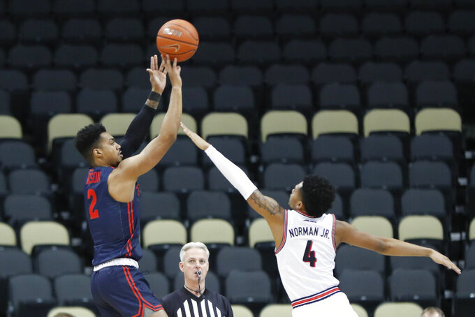 Dayton's Ibi Watson (2) shoots a 3-pointer as Duquesne's Lamar Norman Jr. (4) defends during the first half of an NCAA college basketball game Wednesday, Jan. 29, 2020, in Pittsburgh. (AP Photo/Keith Srakocic)