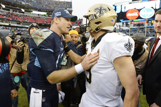 Tennessee Titans quarterback Ryan Tannehill, left, and New Orleans Saints quarterback Drew Brees meet on the field after an NFL football game Sunday, Dec. 22, 2019, in Nashville, Tenn. The Saints won 38-28. (AP Photo/Mark Zaleski)