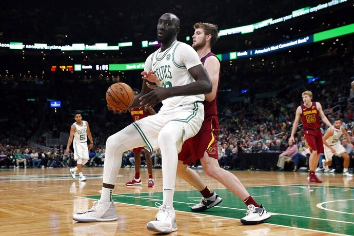 FILE - In this Oct. 13, 2019, file photo, Boston Celtics' Tacko Fall, left, looks to move against Cleveland Cavaliers' Dean Wade during the second half of an NBA preseason basketball game in Boston. Tacko Fall _ a two-way signee for the Celtics, at 7-foot-5 unquestionably the biggest man and most probably the biggest name in the G League to open this season _ might be the next in a rapidly growing line of G League success stories. The two-way contract has been a valuable tool for NBA clubs and players. (AP Photo/Michael Dwyer, File)