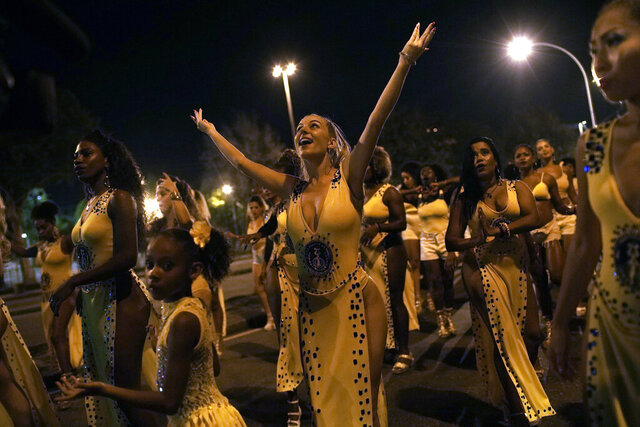 In this Jan. 27, 2020 photo, Jessica Hahn-Chaplin, center, from Bristol, England, dances during a rehearsal of the Paraiso de Tuiuti samba school in Rio de Janeiro, Brazil. Hahn-Chaplin is part of the movement of foreigners who flock to Brazil to train in the ways of the hip swiveling and hot stepping rhythms of samba. (AP Photo/Silvia Izquierdo)
