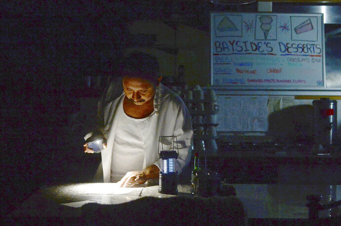 Carlos Lama of Bayside Cafe, which was among businesses to lose power due to PG&E's public safety power shutoff, uses an LED lamp and light from his phone at the counter of the restaurant in Sausalito, Calif., Wednesday, Oct. 9, 2019. More than a million people in California were without electricity Wednesday as the state's largest utility pulled the plug to prevent a repeat of the past two years when windblown power lines sparked deadly wildfires that destroyed thousands of homes. (Alan Dep/Marin Independent Journal via AP)