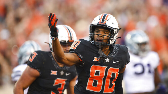 Oklahoma State wide receiver Brennan Presley (80) gestures to the crowd following a pass he caught for a touchdown, during the first half of an NCAA college football game against Kansas State, Saturday, Sept. 25, 2021, in Stillwater, Okla. (AP Photo/Brody Schmidt)