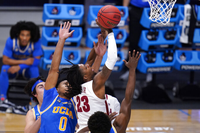 Alabama guard John Petty Jr. (23) tries to shoot against UCLA guard Jaylen Clark (0) in the first half of a Sweet 16 game in the NCAA men's college basketball tournament at Hinkle Fieldhouse in Indianapolis, Sunday, March 28, 2021. (AP Photo/Michael Conroy)