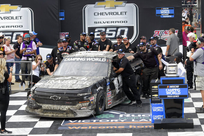 Team members push the car driven by Tate Fogleman into Victory Lane after it was wrecked on the last lap during a NASCAR Truck Series auto race Saturday, Oct. 2, 2021, in Talladega, Ala. Winning driver Fogleman was being checked out in the care center and later was brought to Victory Lane. (AP Photo/John Amis)