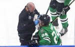 A trainer tends to Dallas Stars' Roope Hintz (24), who had hit the boards during the second period against the Tampa Bay Lightning in Game 4 of the NHL hockey Stanley Cup Final, Friday, Sept. 25, 2020, in Edmonton, Alberta. (Jason Franson/The Canadian Press via AP)