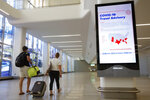 Arriving travelers walk by a sign in the baggage claim area of Terminal B at LaGuardia Airport, Thursday, June 25, 2020, in New York. New York, Connecticut and New Jersey are asking visitors from states with high coronavirus infection rates to quarantine for 14 days. The