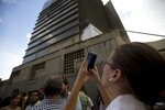 Manuela Bolivar, a lawmaker and member of the First Justice party, takes photos of the Bolivarian National Security Service (SEBIN) headquarters in Caracas, Venezuela, Monday, Oct. 8, 2018. Venezuela's Attorney General Tarek William Saab said Monday that councilman Fernando Alberto Alban Salazar, who was arrested on suspicion of involvement in a failed assassination attempt on President Nicolas Maduro, has died of suicide while jailed at SEBIN. (AP Photo/Fernando Llano)