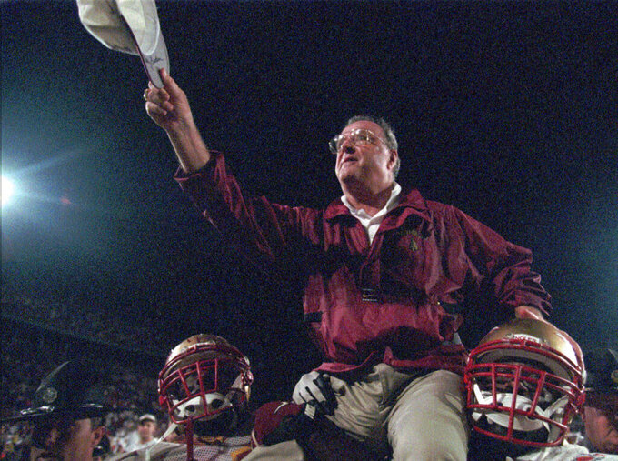 FILE -In this Jan. 1, 1996, file photo, Florida State head coach Bobby Bowden is carried off the field by players after his team won the 62nd annual Orange Bowl against Notre Dame, 31-26, in Miami. Bowden, the folksy Hall of Fame coach who built Florida State into an unprecedented college football dynasty, has died. He was 91. Bobby's son, Terry, confirmed to The Associated Press that his father died at home in Tallahassee, Fla., surrounded by family early Sunday, Aug. 8, 2021. (AP Photo/Jeffrey Boan, File)