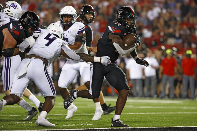 Texas Tech's Xavier White (14) scores a touchdown during the second half of the team's NCAA college football game against Stephen F. Austin, Saturday, Sept. 11, 2021, in Lubbock, Texas. (AP Photo/Brad Tollefson)